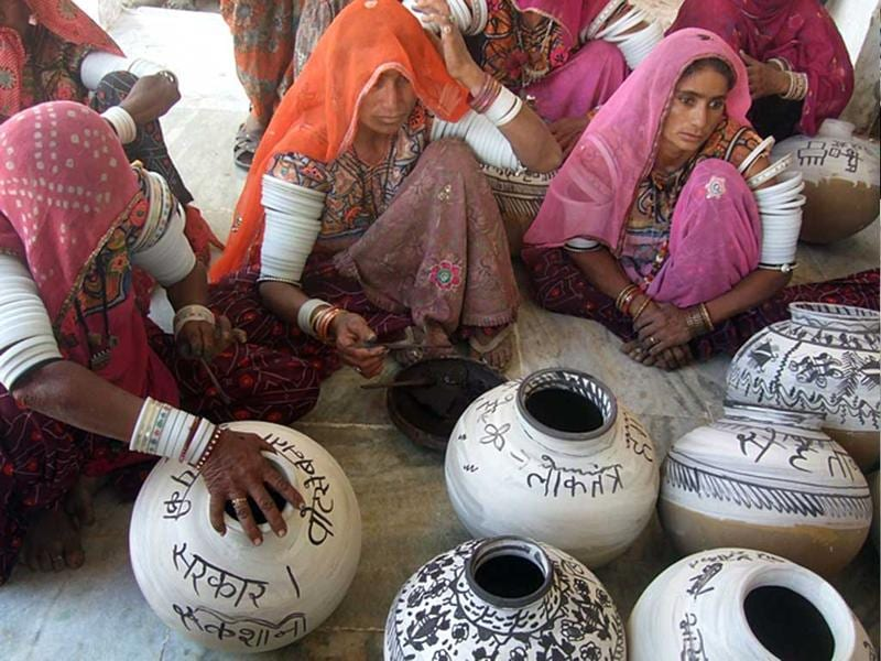 Women paint messages on an earthen pot during a programme conducted by election department to spread awareness about electoral process and to increase voting percentage, in Barmer. (HT Photo)