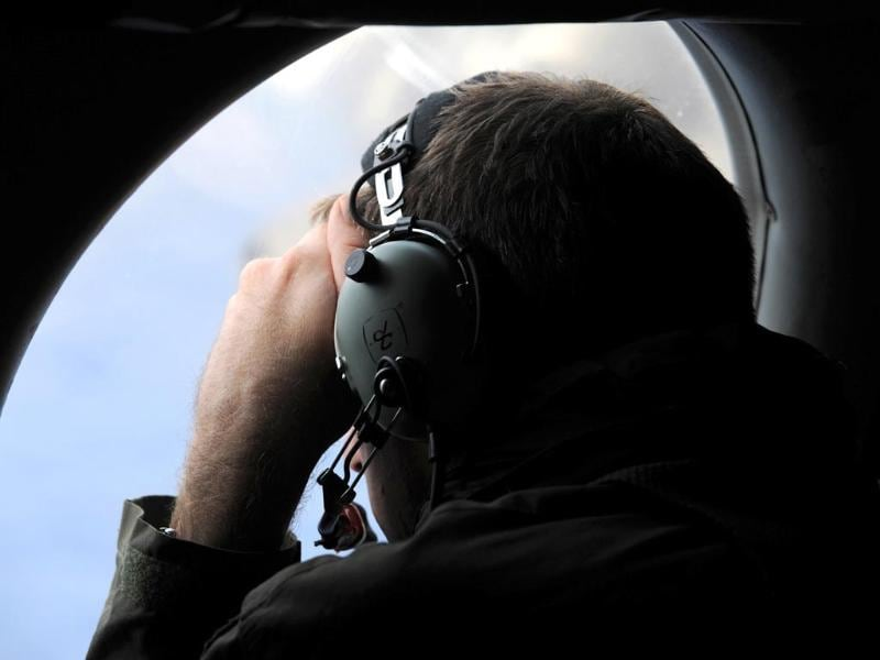 A crew member aboard a Royal New Zealand Air Force (RNZAF) P-3K2 Orion aircraft looks out an observation window as they fly over the southern Indian Ocean to continue the search for missing Malaysian Airlines flight MH370. (Reuters)