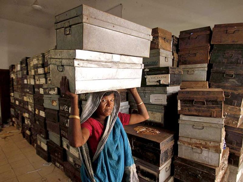 A daily wage woman laborer carries metal boxes containing election material at a distribution center in Bhubaneswar. (AP Photo)