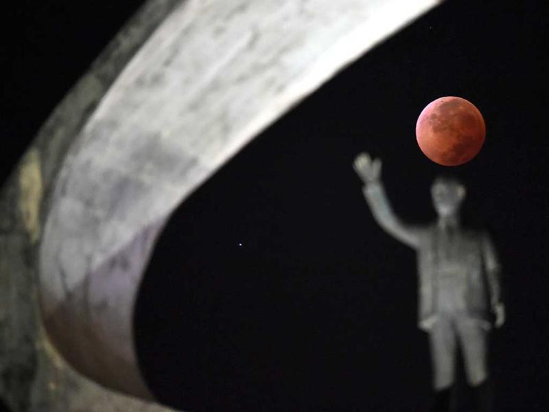 Shows the moon during a total lunar eclipse over the Juscelino Kubitschek Memorial in Brasilia. (AFP Photo)