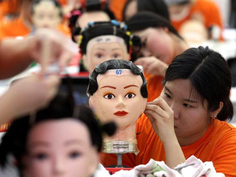 Hairdressers use mannequins to pin-curl during a competition at the K-Beauty World Fashion Festival in Gwacheon, South Korea. About 15,000 makeup artists, hairdressers, fashion designers and aestheticians from 56 countries participated in the annual event to promote the Korean culture. (AP)