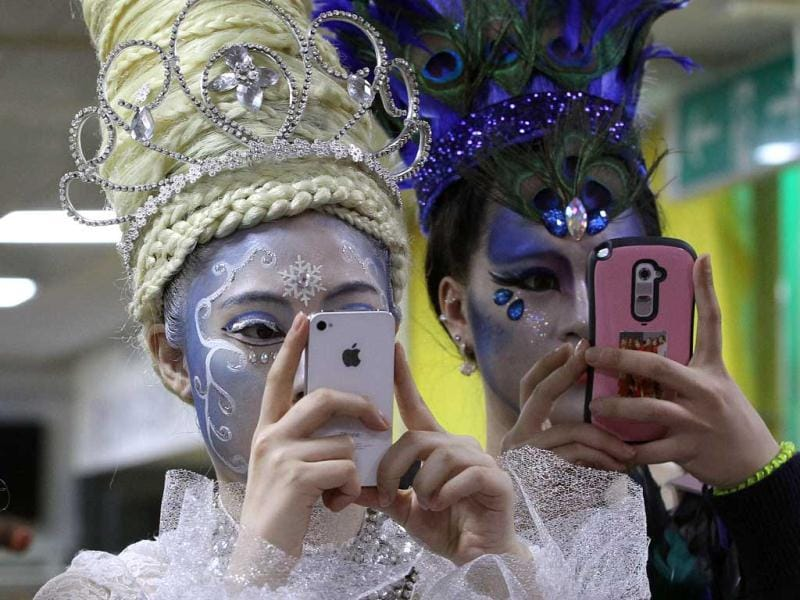 Models with smartphones take pictures of their colleagues during the K-Beauty World Fashion Festival in Gwacheon, South Korea. About 15,000 makeup artists, hairdressers, fashion designers and estheticians from 56 countries participated in the annual event to promote the Korea culture. (AP)