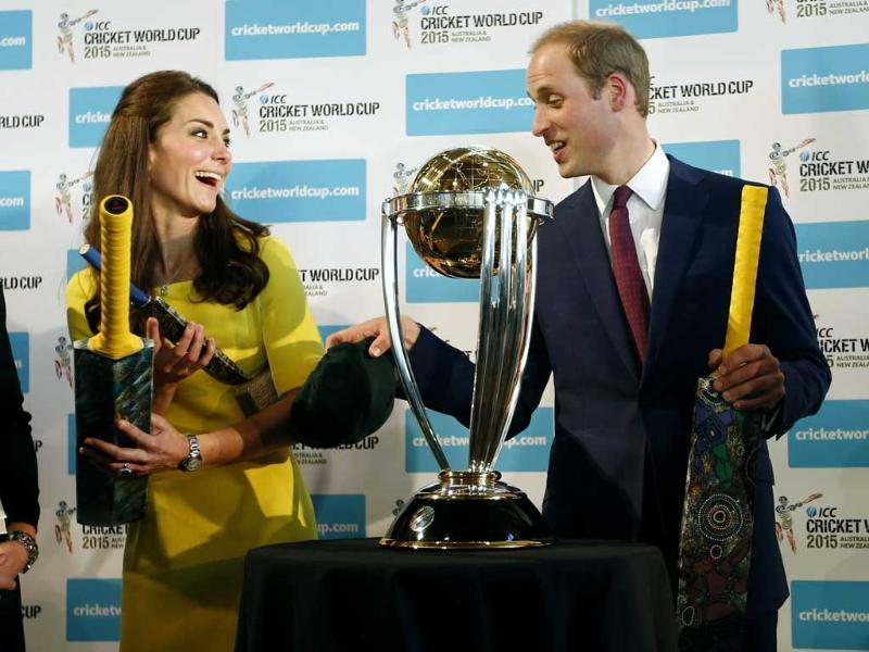 Britain's Prince William and his wife Kate, the Duchess of Cambridge, hold cricket bats presented to them in front of the World Cup during a reception at the Sydney Opera House. (AP photo)