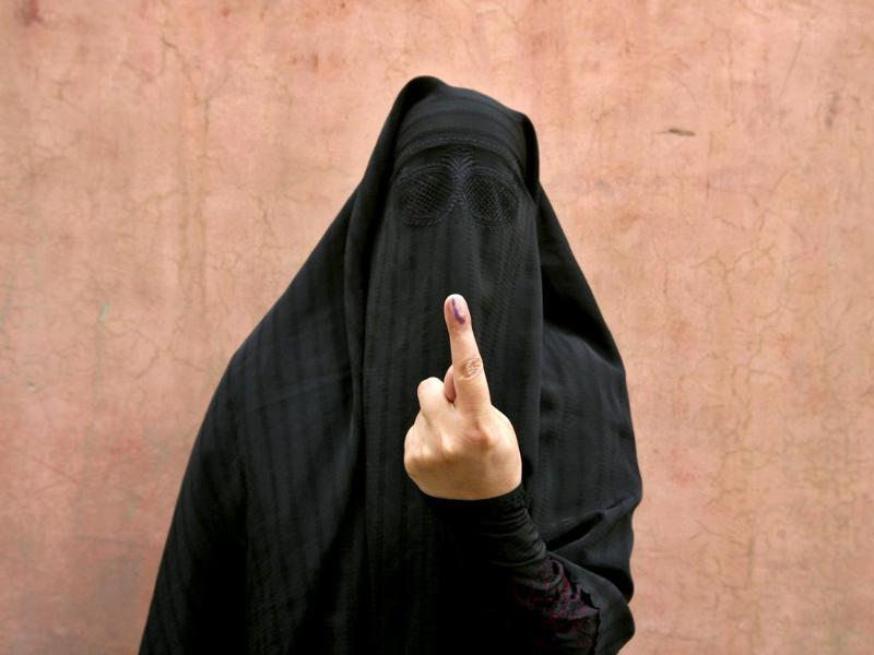 A veiled Muslim woman shows her ink-marked finger after voting outside a polling station in Doda district, north of Jammu. (Reuters)