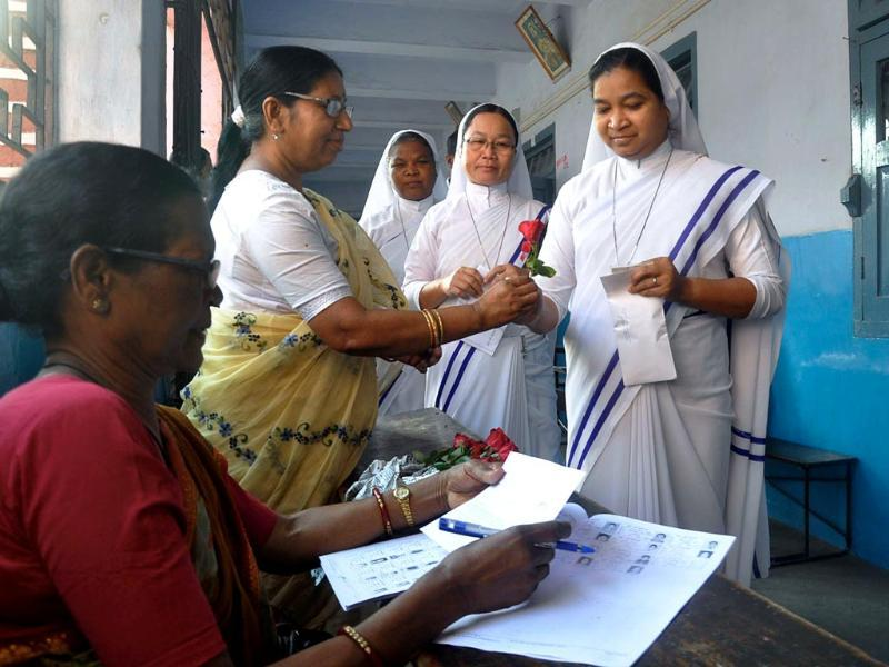 An election official distributes red roses to Christian Nuns during voter registration in Ranchi. (AFP photo)