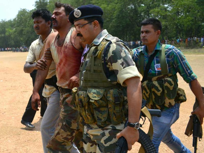Injured CRPF commander Sanjay Kumar is being taken by jawan in Swang in Bokaro district after a Maoist attack near Lalpania. (HT photo/Krishna)