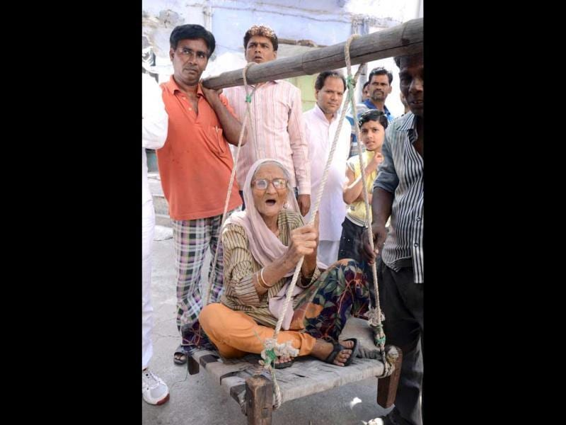 Basheeran Bai (92) is being carried by her family members as she arrives to cast her vote in Lok Sabha polls, in Kota, Rajasthan. (HT photo/AH Zaidi)
