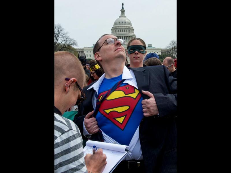 A man identifies his hidden super-hero identity at the Awesome Con 2014 in Washington, DC during an attempt to break a Guinness world records record of people as comic book charactors. (AFP photo)