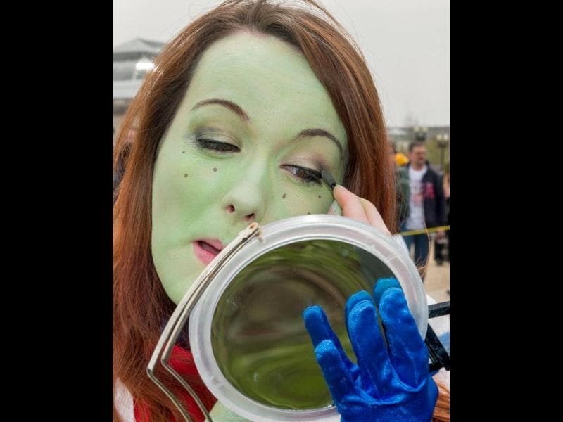 A young women checks her green make-up as she gathers with people dressed in superhero-style costumes at Awesome Con 2014 in Washington. (AFP photo)
