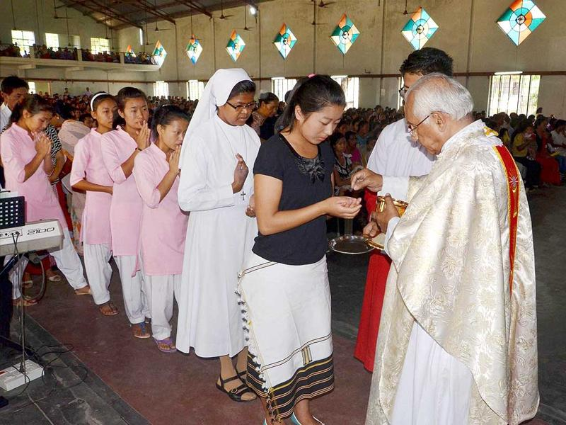 Catholic priest offers Holy Communion during the Easter Sunday Mass at the Holy Cross church in Dimapur, Nagaland.(PTI Photo)
