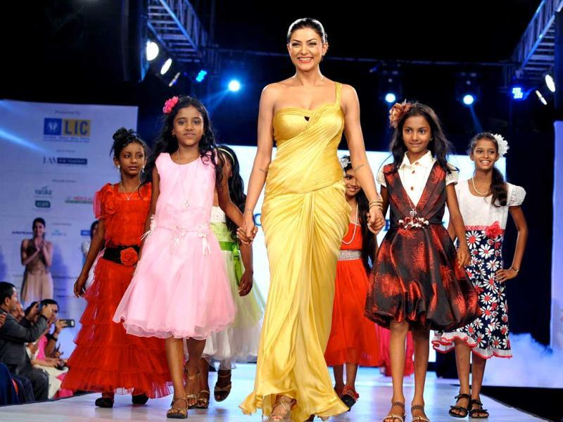 Actor Susmita Sen walks with young girls as she showcases a creation by designer Sonaakshi Raaj during the fifth edition of the Smile Foundation charity fashion show 'Ramp for Champs' to raise support for the education of the girl child, in Mumbai. (AFP)