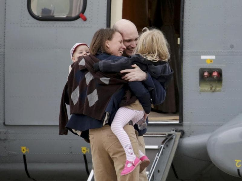 Nicolas Henin (2 R), French journalist, is greeted by his family moments after the arrival of the ex-hostages by helicopter from Evreux to the military airbase in Villacoulbay, near Paris. (Reuters Photo)