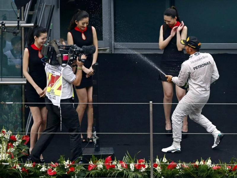 First-placed Mercedes Formula One driver Lewis Hamilton of Britain sprays champagne to grid girls as he celebrates his win after the Chinese F1 Grand Prix at the Shanghai International circuit. (Reuters Photo)