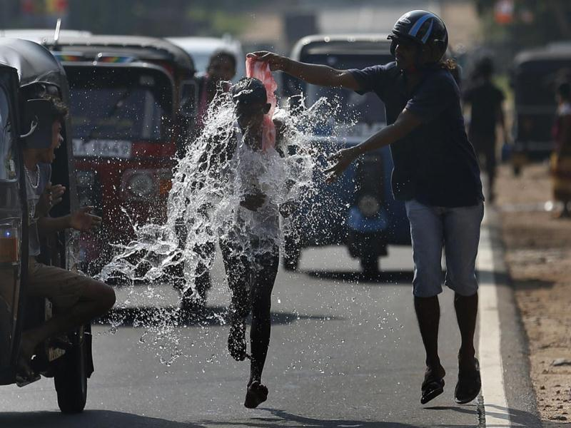 A man pours water on a competitor during a road race as part of traditional festival games to celebrate the Sinhala, the Hindu and Tamil New Year, in Homagama. (Reuters Photo)