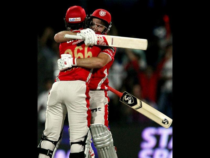 David Miller of Kings X1 Punjab with teammate Cheteshwar Pujara celebrate their win over Rajasthan Royals in their IPL 7 match in Sharjah. (PTI Photo)