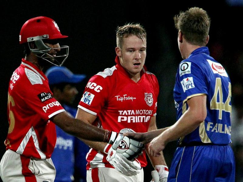 David Miller of Kings X1 Punjab with teammate Cheteshwar Pujara shake hands with James Faulkner of Rajatshan Royals after theirIPL 7 match in Sharjah. (PTI Photo)