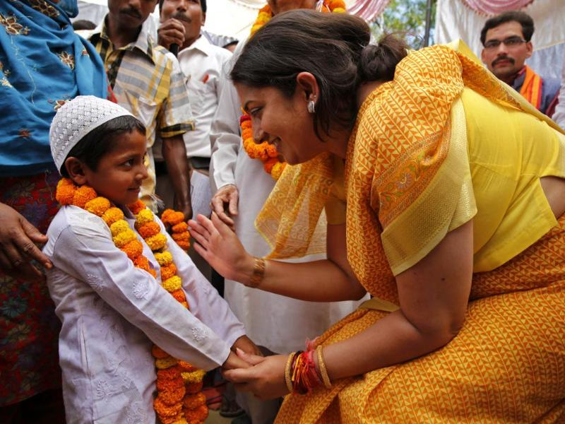 BJP candidate Smriti Irani, talks to a young Muslim boy at an election rally in Amethi (AP Photo)
