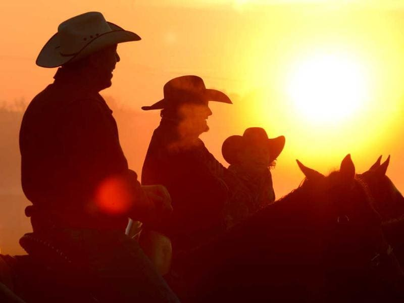 Worshippers join together for a sunrise service at the No Fences Cowboy Church Easter Sunday in Falkville, Alabama. Cowboys on horseback greet the sunrise and arriving worshippers. (AP Photo)