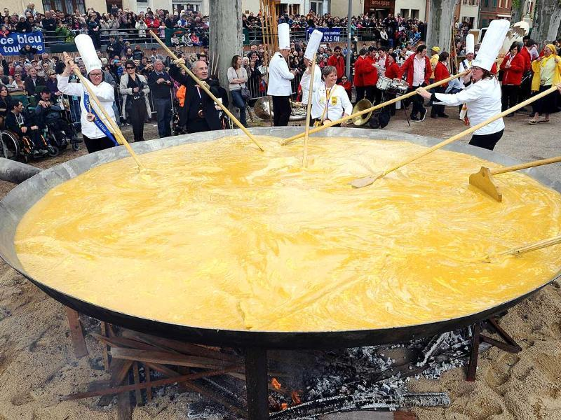 Members of the brotherhood of the Bessieres' giant Easter omelette prepare a giant omelette with thousands of eggs, in southwestern France, as part of a traditional Easter celebration. (AFP Photo)