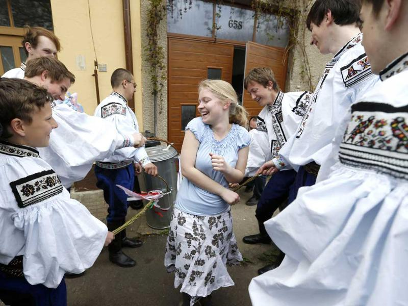 Andrea Slavotinkova is whipped by a group of young men dressed in traditional costumes celebrating Easter Monday in the village of Vlcnov, Southern Moravia, Czech Republic. The tradition of whipping girls and women with plaited willow stems, on Easter, should assure her of good health, fresh look and keep fertility. (AP Photo)