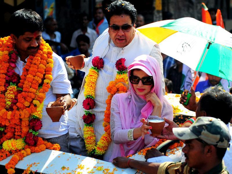 Amisha Patel receives sweets from a supporter during an election roadshow for Congress candidate for Allahabad parliamentary constituency Nand Gopal Gupta in Allahabad. (AFP)