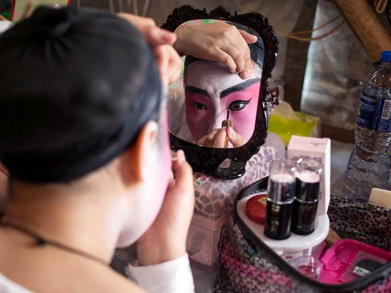 A Chinese Cantonese opera singer applies her make-up before performing during the Tin Hau festival on Lamma Island, an outlying island of Hong Kong (AFP Photo)