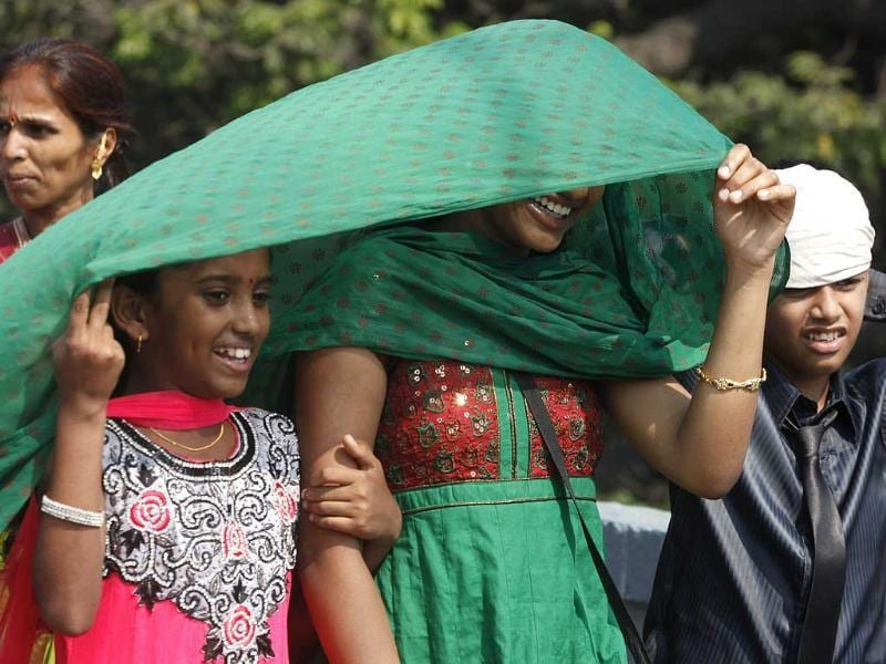 Girls protecting their face with a stole to escape from heat at Matunga in Mumbai. (HT photo/Kunal Patil/)