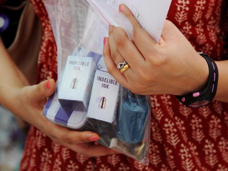 EC staff member holds an envelope containing polling material after collecting an electronic voting machine and other election material at a distribution centre on the eve of polls in Mumbai. (AFP photo)