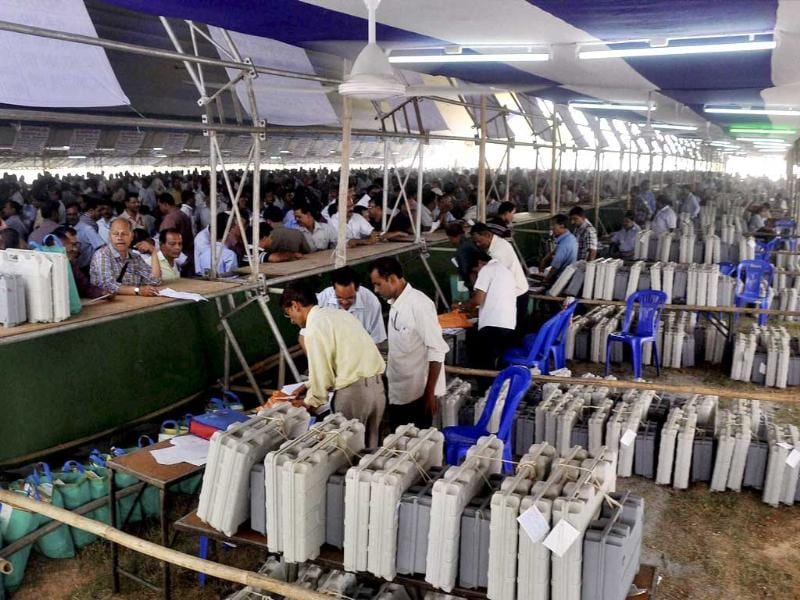 Poll officials waiting in queues to collect EVMs from a distribution centre at Saruhozai on the eve of Lok Sabha elections in Guwahati. (PTI photo)