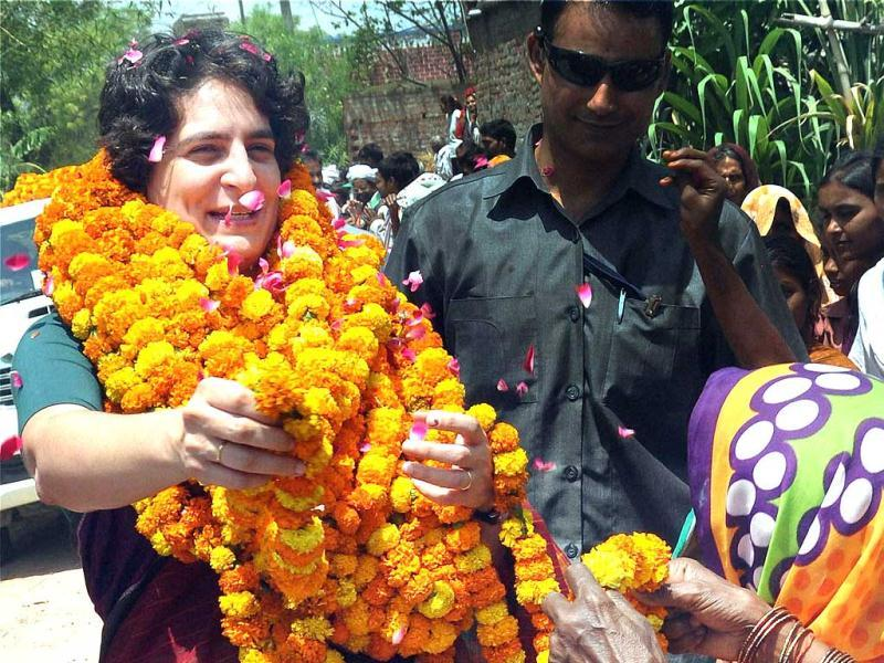 Priyanka Vadra receives garland from a woman at an election campaign meeting for her mother and Congress president Sonia Gandhi in Raebareli. (PTI photo)