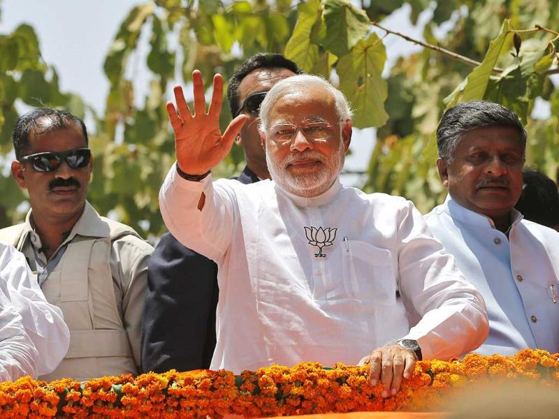 BJP PM candidate Narendra Modi greets supporters at a road show before filing his nomination papers in Varanasi. (PTI photo)