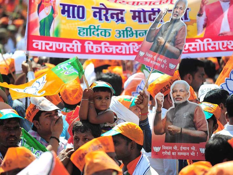 BJP supporters during a road show by BJP PM candidate Narendra Modi before filing his nomination papers in Varanasi. (PTI photo)