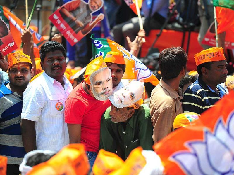 Supporters of BJP prime ministerial candidate Narendra Modi wait for his arrival to file his nomination papers in Varanasi. (AFP photo)