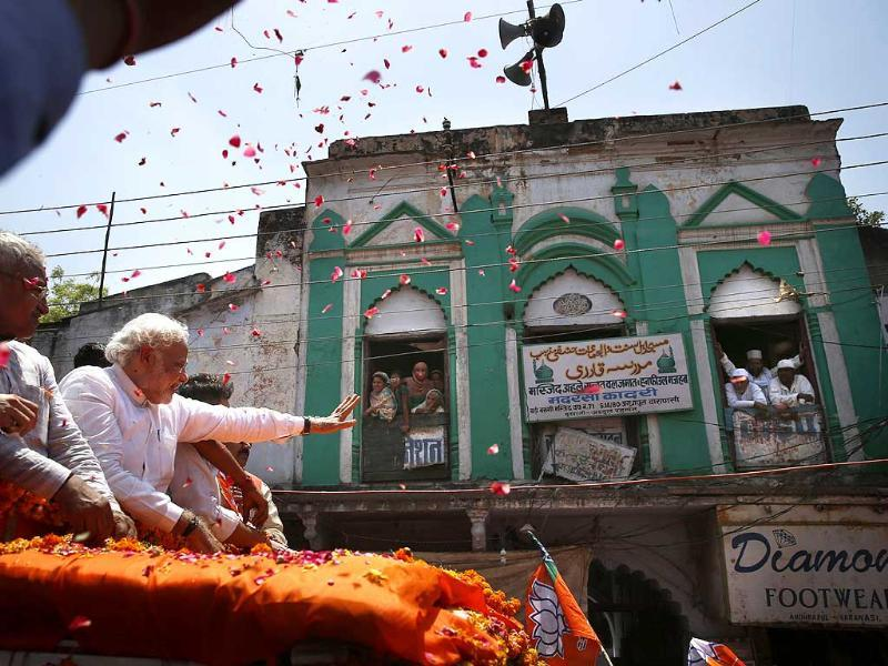 BJP prime ministerial candidate Narendra Modi greets supporters as he moves past a mosque on his way to submit nominations at Varanasi. (AP photo)