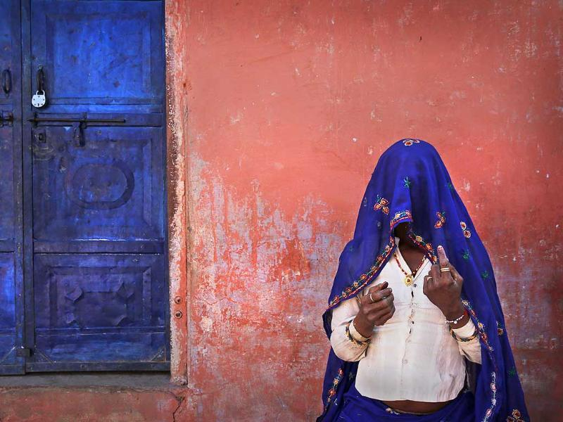 A woman shows her finger marked with indelible ink after casting her vote during the 6 phase of polling of the Lok Sabha elections at a village near Sawai Madhopur, Rajasthan. (AP photo)