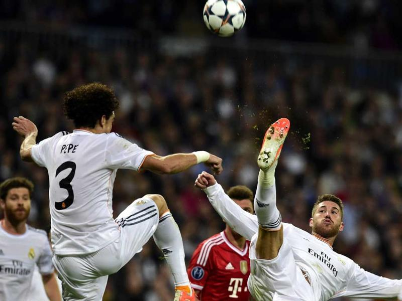 Real Madrid's defender Sergio Ramos (R) jumps to kick the ball past Pepe during the UEFA Champions League semifinal first leg match Real Madrid CF vs FC Bayern Munchen in Madrid. (AFP photo)