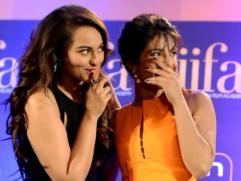 Priyanka Chopra and Sonakshi Sinha, nominee for best performance in a leading role, laugh during a press conference at the Hilton Downtown Hotel on the second day of the 15th International Indian Film Academy (IIFA) awards in Tampa, Florida. (AFP)