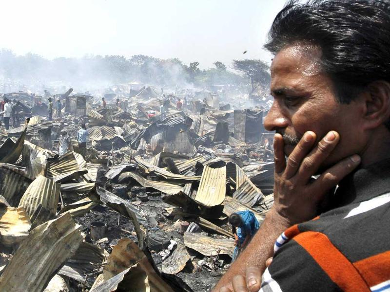 A man looks at his burnt house after the fire in JJ cluster at Vasant Kunj, in New Delhi. (HT photo/Sanjeev Verma)