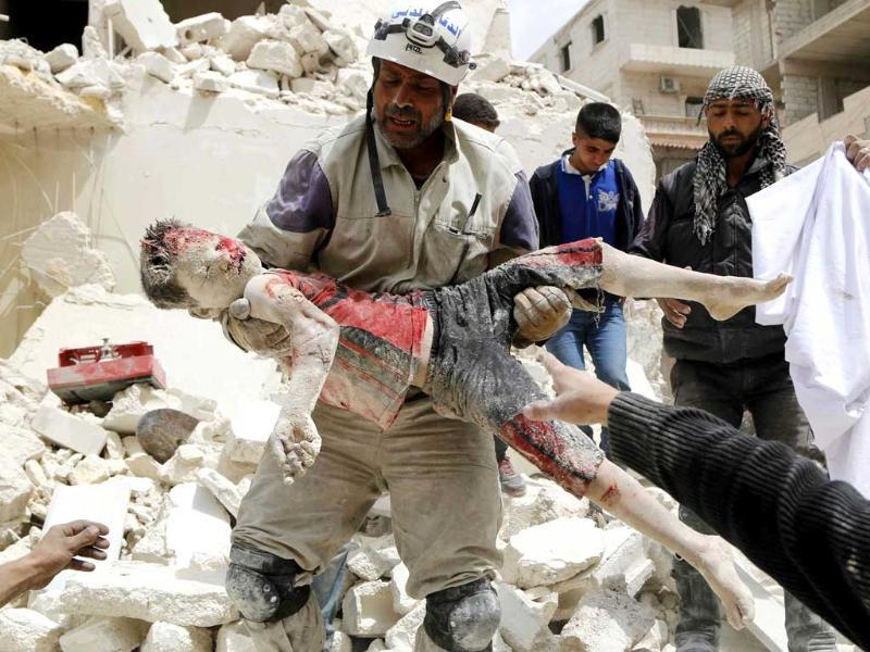 A rescuer carries a dead boy after what activists said was a barrel bomb dropped by forces loyal to Syria's President Bashar al-Assad in Aleppo's Karam al-Beik neighborhood. (Reuters photo)
