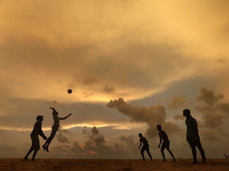A man jumps to hit the ball while playing beach volleyball on a beach in Colombo. (Reuters photo)