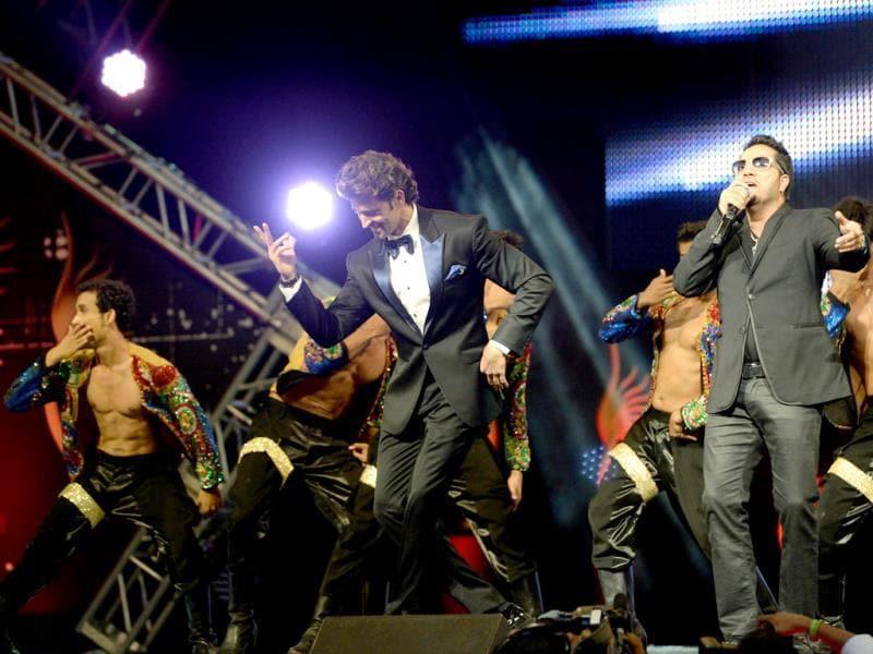 Hrithik Roshan dances with Mika Singh on stage during the IIFA Magic of the Movies show at IIFA Awards. (AFP)