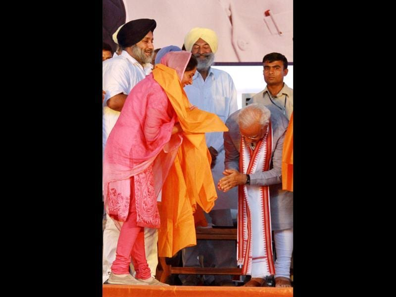 BJP's PM candidate Narendra Modi gestures after SAD candidate Harsimrat Kaur Badal touched his feet during an election rally in Bathinda. (PTI Photo)
