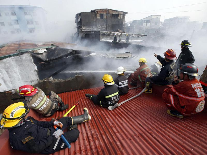Firemen keep watch on a rooftop next to an apartment building on fire to prevent it from spreading, in Manila. (Reuters photo)
