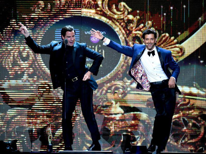 Hollywood actor John Travolta (L) shows Bollywood actor Hrithik Roshan a dance step on stage during the fourth and final day of the 15th International Indian Film Academy (IIFA) Awards at the Raymond James Stadium in Tampa, Florida. (AFP)