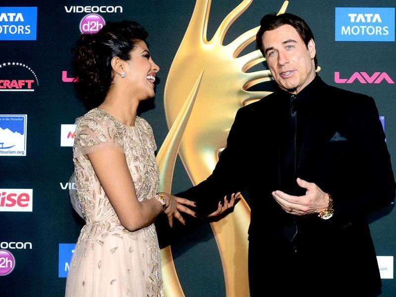 US actor John Travolta poses with Bollywood actress Priyanka Chopra pose on the green carpet at the Raymond James Stadium on the fourth and final day of the 15th International Indian Film Academy (IIFA) Awards in Tampa, Florida. (AFP)