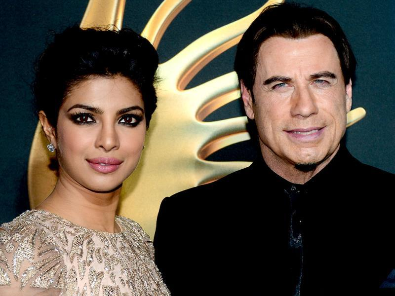 US actor John Travolta poses with Bollywood actress Priyanka Chopra on the green carpet at the Raymond James Stadium on the fourth and final day of the 15th International Indian Film Academy (IIFA) Awards in Tampa, Floridaon April 26, 2014. (AFP)