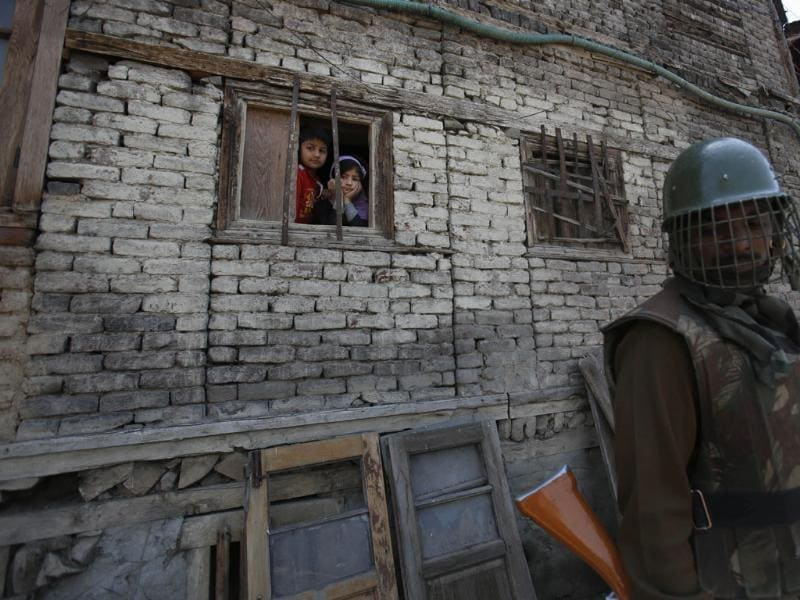 An Indian paramilitary soldier stands guard as Kashmiri children look through a window of their house during an election campaign rally by Jammu-Kashmir state's governing National Conference party leader Farooq Abdullah, in Srinagar. (AP Photo)