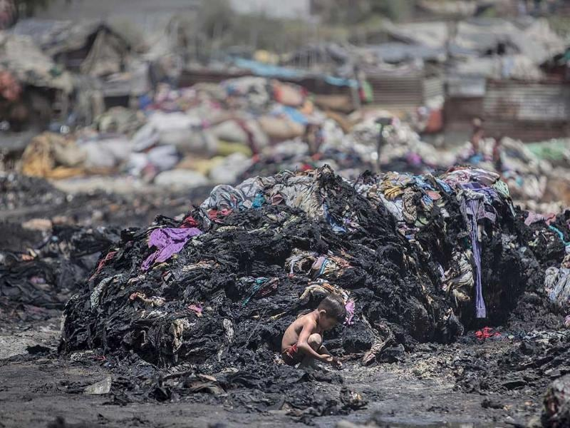An Indian boy looks for metal scrap amid charred debris after a fire at a slum in Ghaziabad, outskirts of New Delhi, India. (AP Photo)