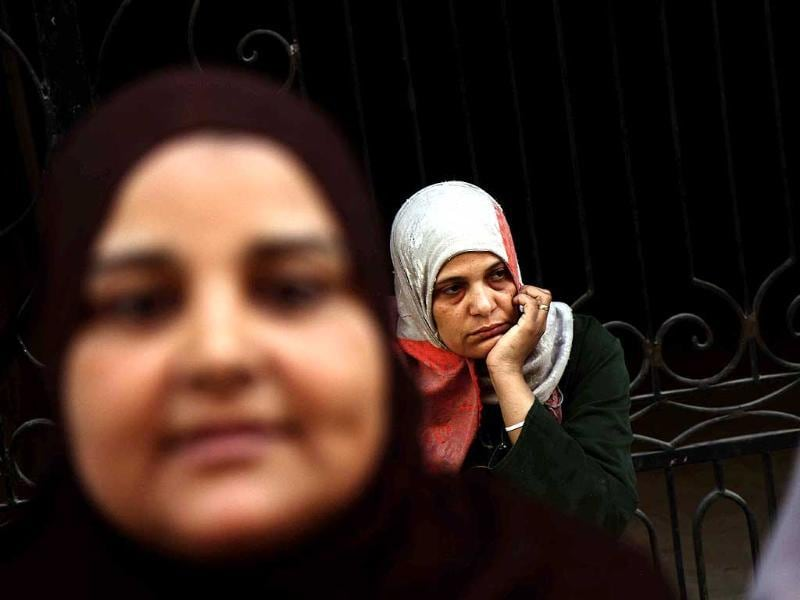 An Egyptian woman looks at women overcome by emotion after a judge in Egypt sentenced to death 683 alleged supporters of the country's ousted Islamist president over acts of violence and the murder of policemen in the latest mass trial in the southern city of Minya, Egypt. (AP Photo)