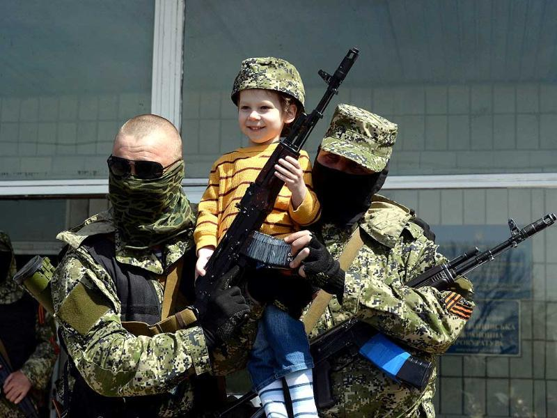Pro-Russian armed men in military fatigues pose for a photograph with a child as they stand guard outside a regional administration building seized in the night by pro-Russian separatists, in the eastern Ukrainian city of Konstantinovka. (AFP Photo)